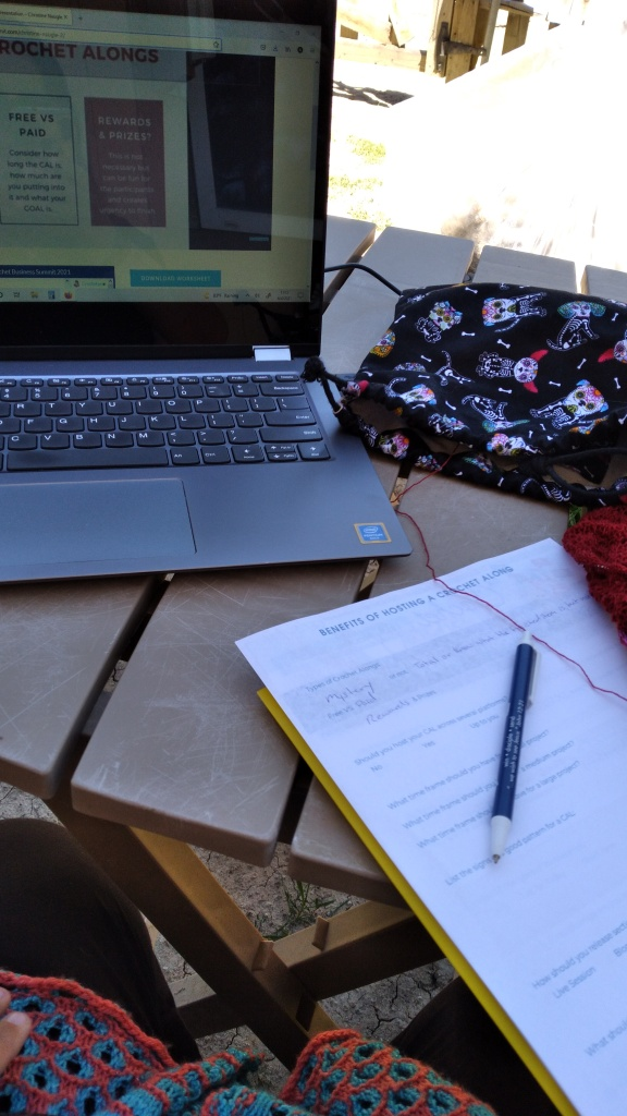 Sara's computer is open on a table outside.  She has her notes for this session of the Crochet Business Summit and her red lace knitting project is off to the right side.