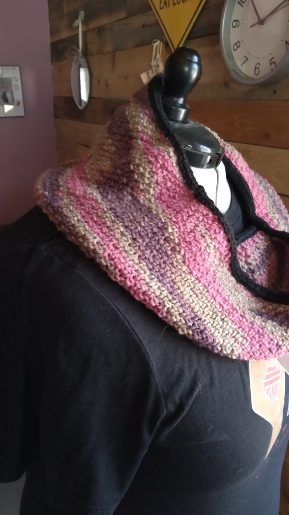 A side view of the finished cowl in purple, pink and gray using seed stitch on a mannequin.