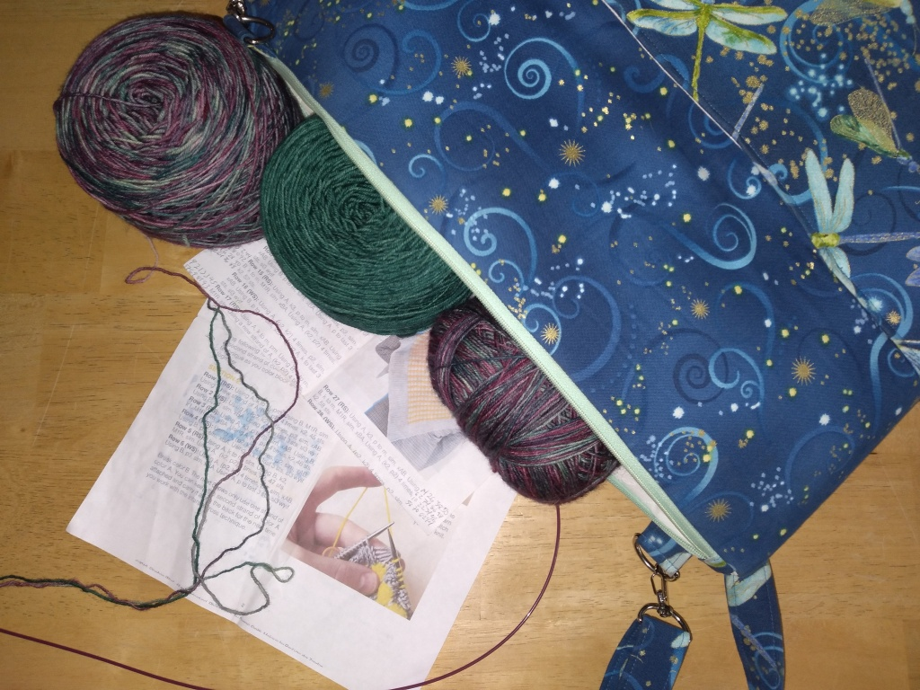 Three balls of yarn spill out of a zippered project bag, decorated with dragon flies.  Water stained directions of the Bubble Shawl pattern can be seen behind the yarn tails and the cable of the needle.