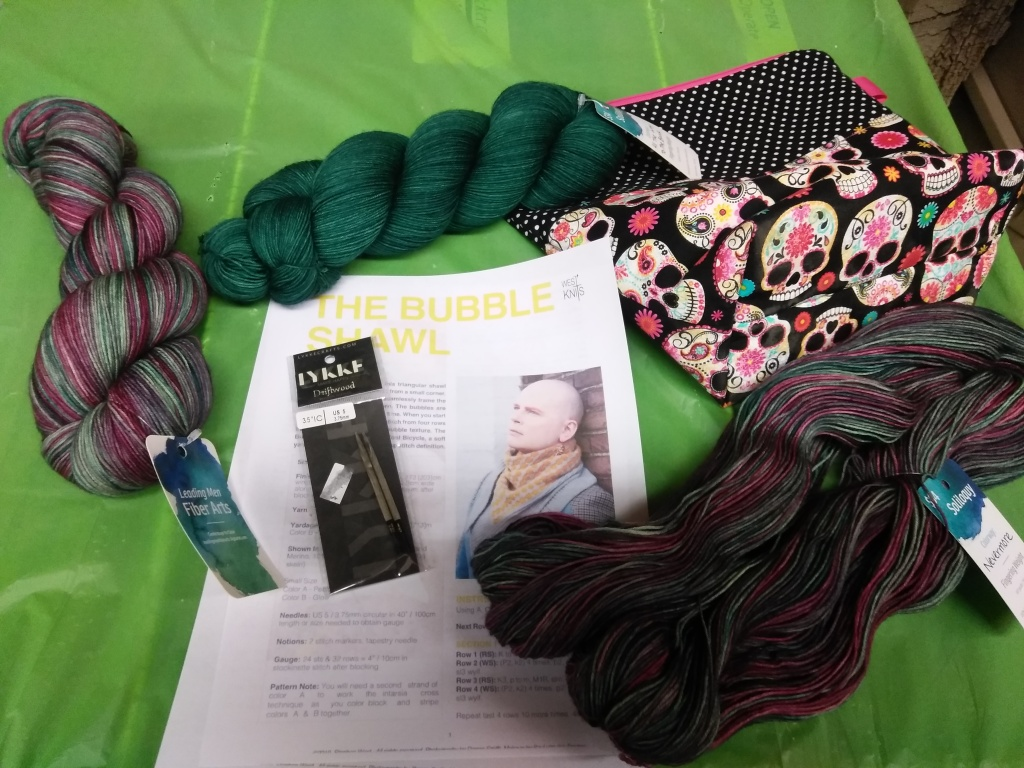 Three hanks of yarn lay on a green background with a set of interchangeable needle tips in the package, The cover of the Bubble shawl pattern visible. A zippered project bag with sugar skulls and polka dots on it is ready to be packed.