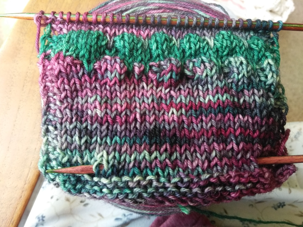 A small swatch of the bubble stitch, worked in variegated yarn, resting on top of a ball of yarn.
